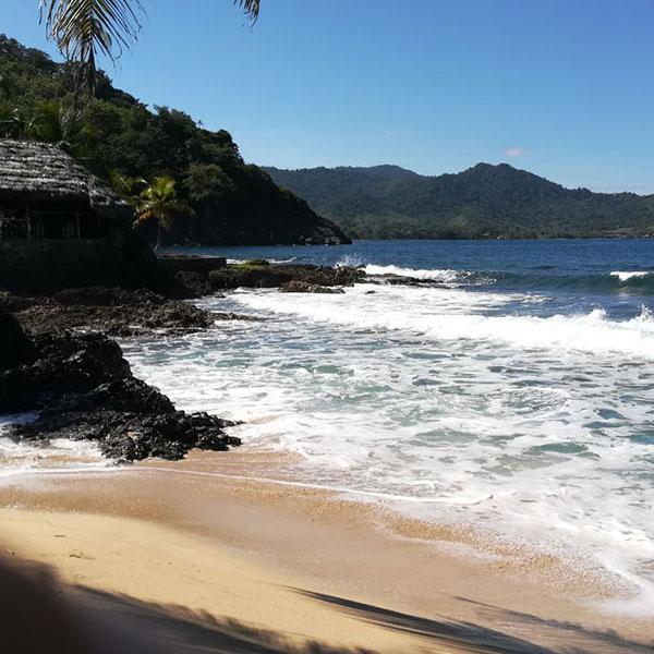 Sandstrand mit brechenden Wellen bei sonnigem Wetter
